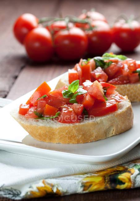 Bruschetta mit in Scheiben geschnittenen Tomaten und Basilikum — Stockfoto