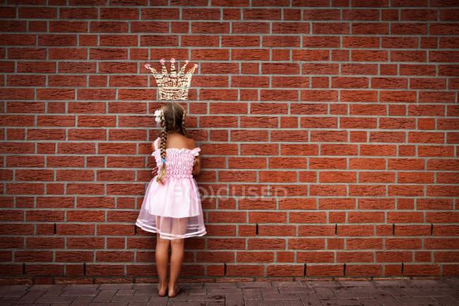 Резервного зору дівчина у сукні стояти під цегляну стіну, принцеси корони звернено на будівлі — стокове фото