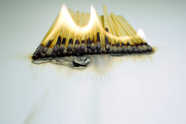 Matchsticks in flame on table surface, burning matchsticks — Stock Photo