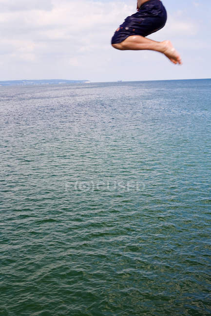 Partial view of man jumping in sea water — Stock Photo