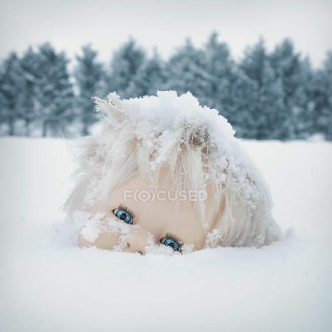 Tête de poupée fantasmagorique dans la neige au sol de la forêt, les arbres sur fond — Photo de stock