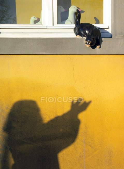 Shadow of girl on yellow house wall, cat toy decoration at window — Stock Photo