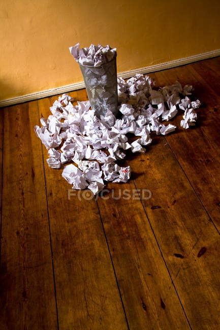 Rumpled papers in trash basket and on wooden floor — Stock Photo