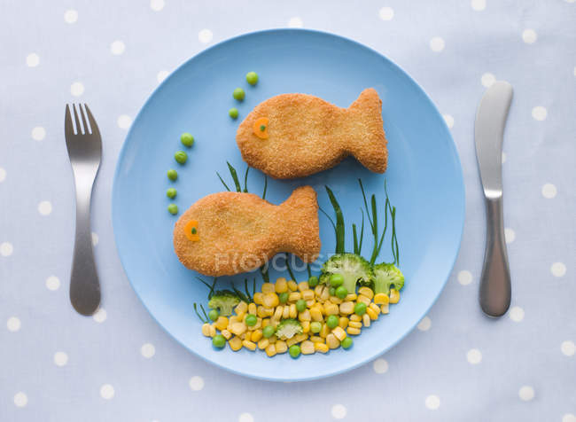 Plato infantil de palitos de pescado con maíz y guisantes - foto de stock