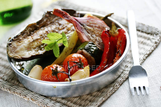 Closeup of grilled vegetables in casserole form with fork on table — Stock Photo