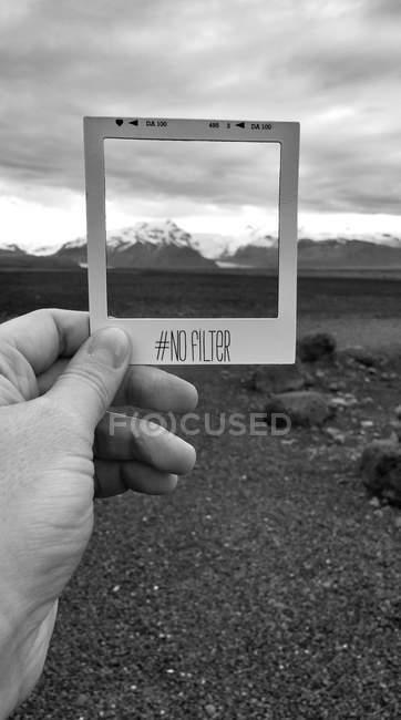Partial view of male hand holding Polaroid frame against mountain range — Stock Photo