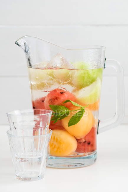 Cold drink, fruits lemonade with mint leaves in jug — Stock Photo