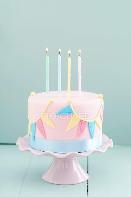 День рождения торт с гирляндой из марципана и горения свечи — стоковое фото
