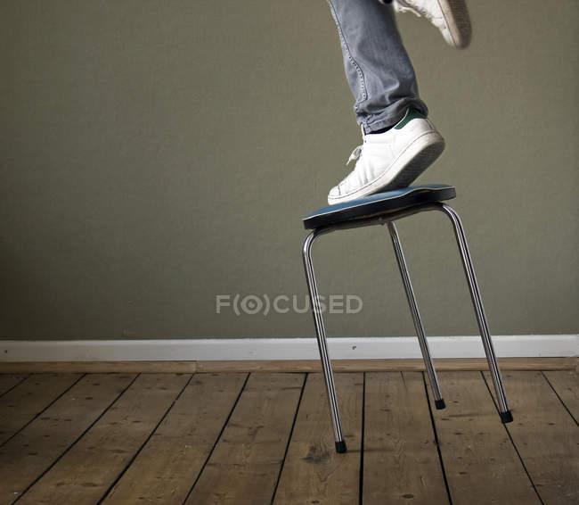 Обрезанный образ человека ноги стоя на падающем стуле в комнате, скольжение падает — стоковое фото