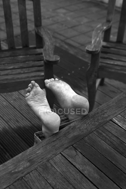 Black and white photo of barefoot feet and wooden table — Stock Photo