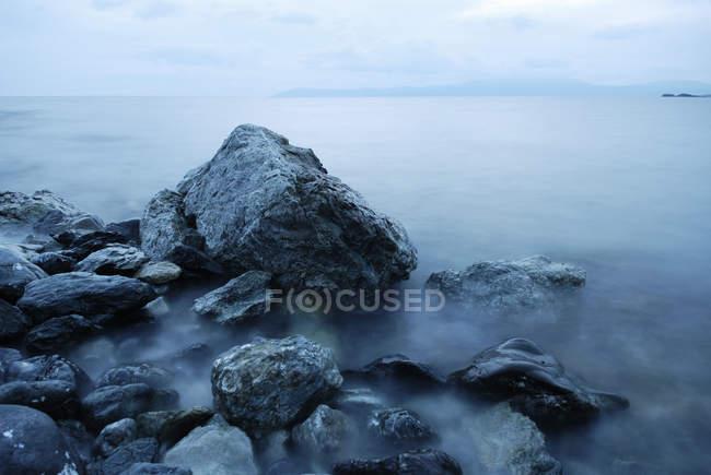 Sea coast with rocks in fog — Stock Photo