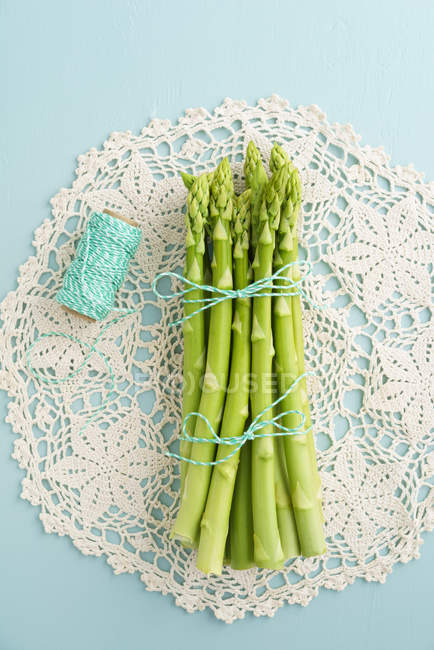 Green asparagus strings on white tray with thread, top view — Stock Photo