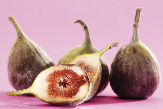 Exotic purple fresh figs in studio on pink surface — Stock Photo