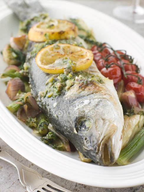 Жареная рыба с дольками лимона и овощами на плите — стоковое фото