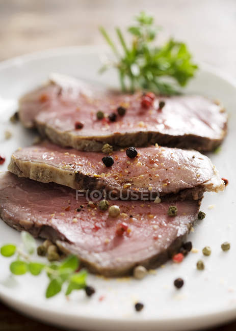 Roast beef slices under herbs and pepper — Stock Photo