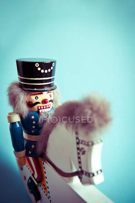 Nutcracker toy on wooden horse and blue background for copy space — Stock Photo