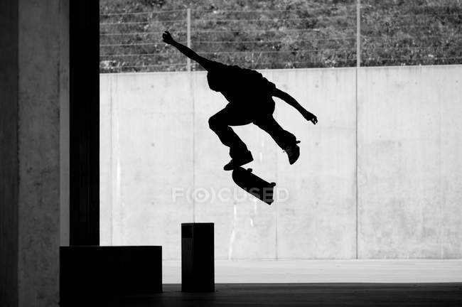 Silhouette of jumping man with skateboard, skating, black and white — Stock Photo
