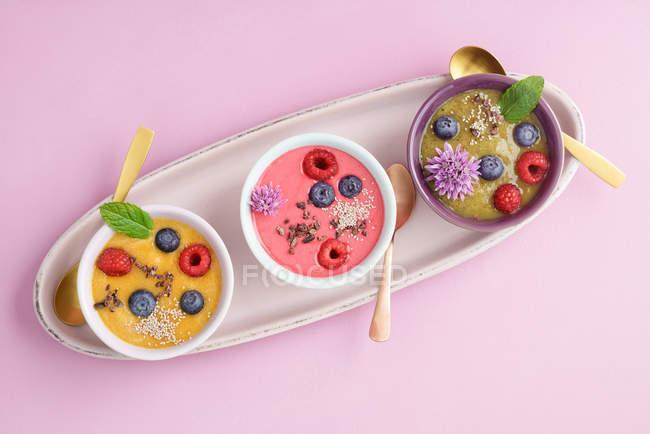 Draufsicht der verschiedenen Smoothie mit Beeren auf Tablett Schalen — Stockfoto