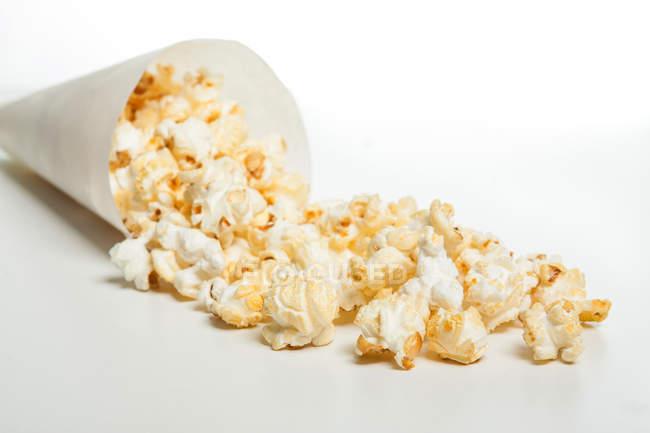 Popcorn aus Papier-Membran auf weiße Fläche ausgegossen — Stockfoto