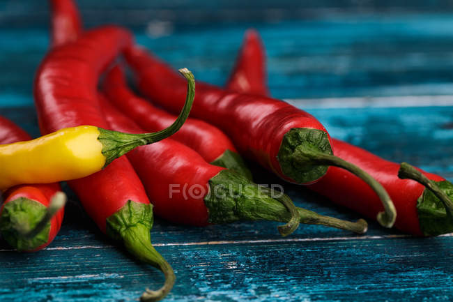 Chili pepperoni peppers on blue wooden table — Stock Photo