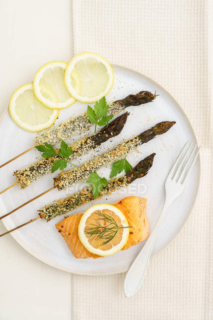 Aspargos, salmão peixe e rodelas de limão na placa — Fotografia de Stock