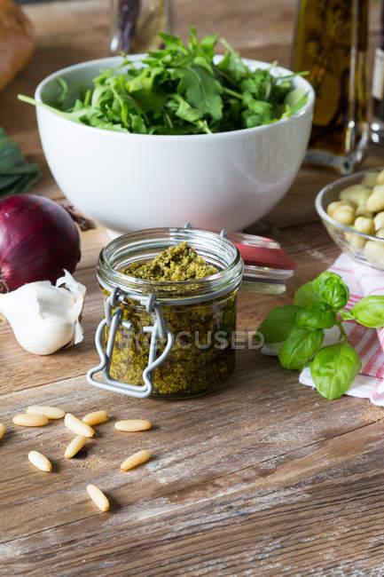 Sauce pesto sur table avec des feuilles de basilic et noix — Photo de stock