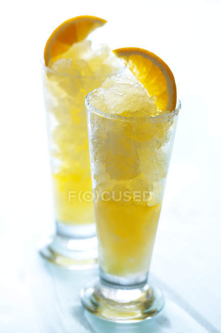 Yellow fruit cocktails with ice and orange slices — Stock Photo