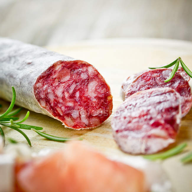 Salami salamis with green rosemary leaves — Stock Photo