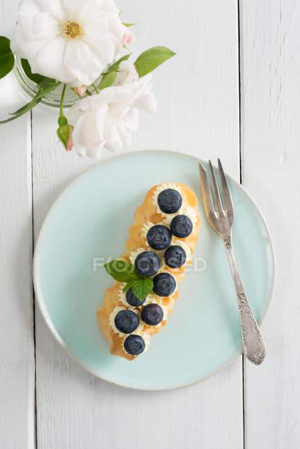 Синий торт пластины с Эклер и голубика — стоковое фото
