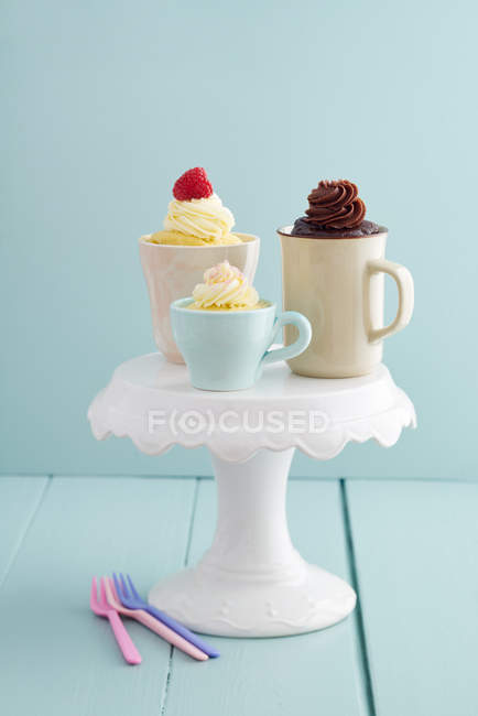 Mug cakes in various cups on stand — Stock Photo