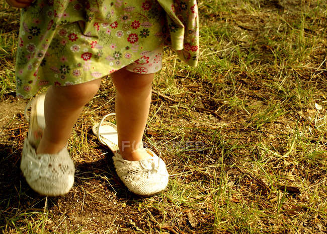 Cropped image of toddler girl in dress walking in green grass meadow — Stock Photo