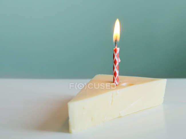 Käsekuchenstück mit brennender Kerze — Stockfoto