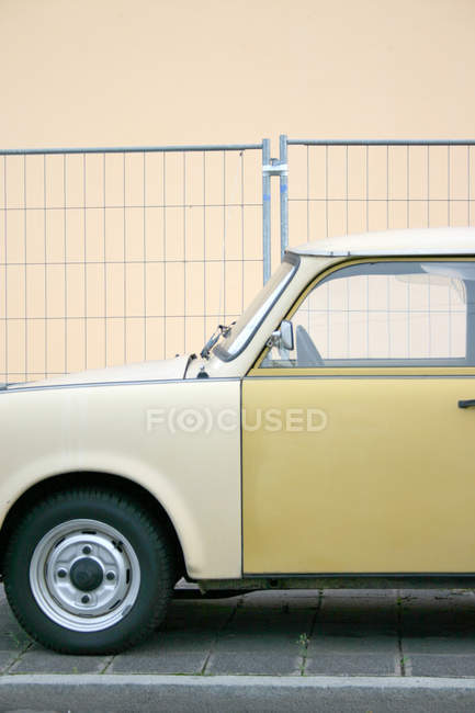 Old fashioned car parked in street at building house wall — Stock Photo