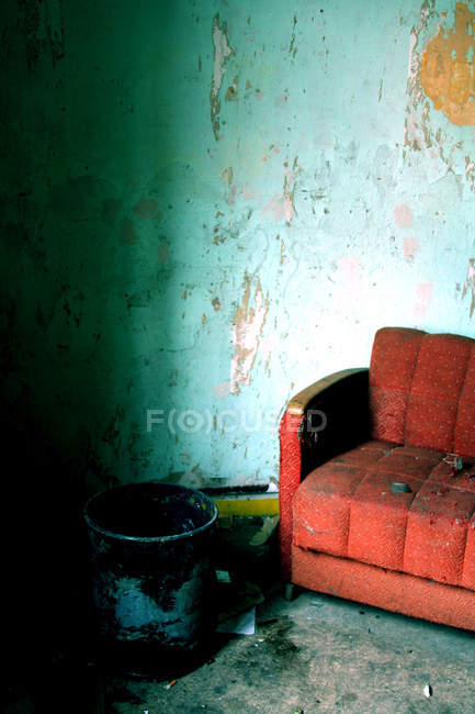 Old apartment room, abandoned place with dirty wall and red old arm chair — Stock Photo