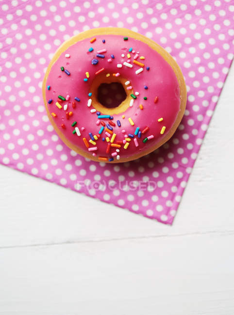 Frosting pink donut on napkin — Stock Photo