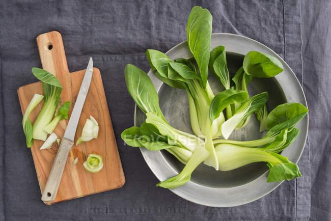 Pak choi chou vert feuilles dans un bol de fer près de planche de bois avec couteau — Photo de stock