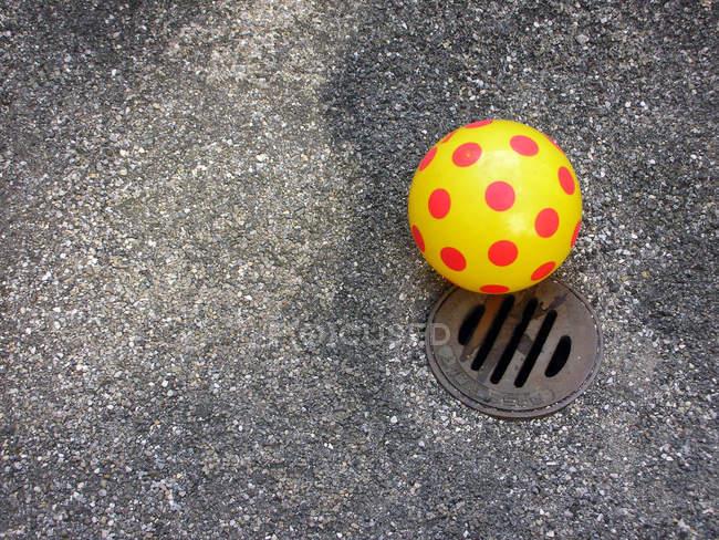 Palla gialla con puntini rossi su strada con tombino — Foto stock