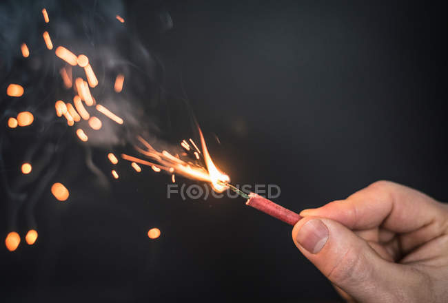 Cropped image of person hand holding burning firework — Stock Photo