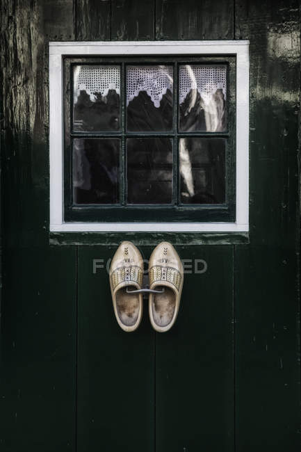 Wooden house window with white curtain and facade with Holland clogs — Stock Photo