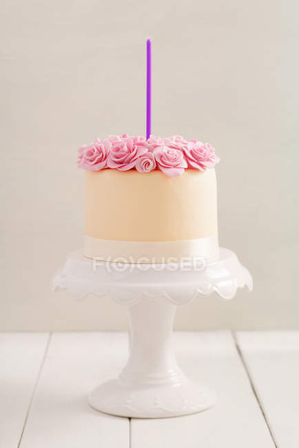 Birthday cake with cream roses decorations and one candle