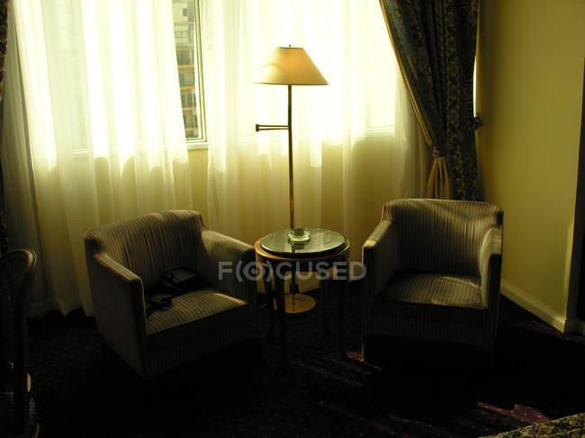 Интерьер комнаты с двумя креслами, лампа на окна шторы — стоковое фото