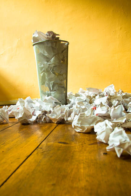 Basket full of wrinkled papers, wooden floor with rumpled papers — Stock Photo