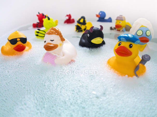 Rubber ducks in bath water with foam — Stock Photo