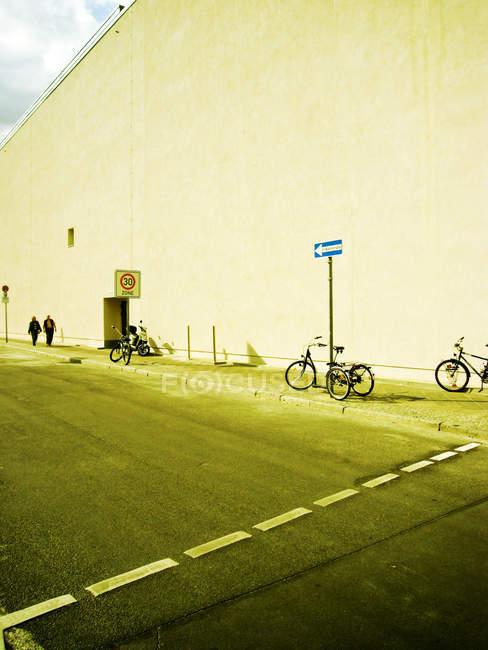 Hauswand mit Straße, Bürgersteig, Fahrräder und Verkehr Schild mit Pfeil — Stockfoto