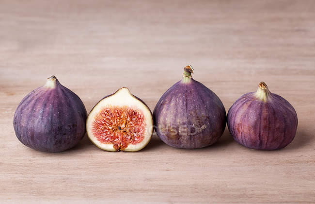Exotic purple fresh figs on wooden surface — Stock Photo