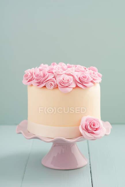 Soporte de la torta con la torta de boda, decorada con flores de rosa de mazapán - foto de stock