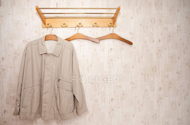Retro wall with hangers, hanging male jacket — Stock Photo