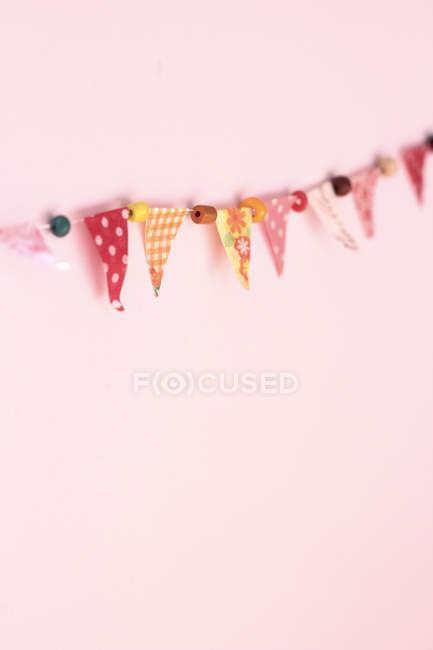 Guirlande de fête colorée sur mur rose — Photo de stock