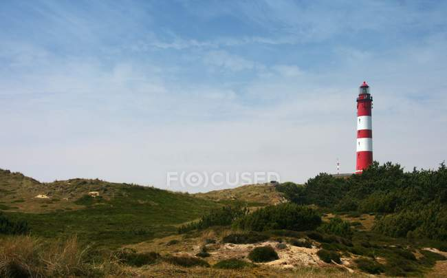 Red and white lighthouse in dune with hills and grass, North Frisia — Stock Photo