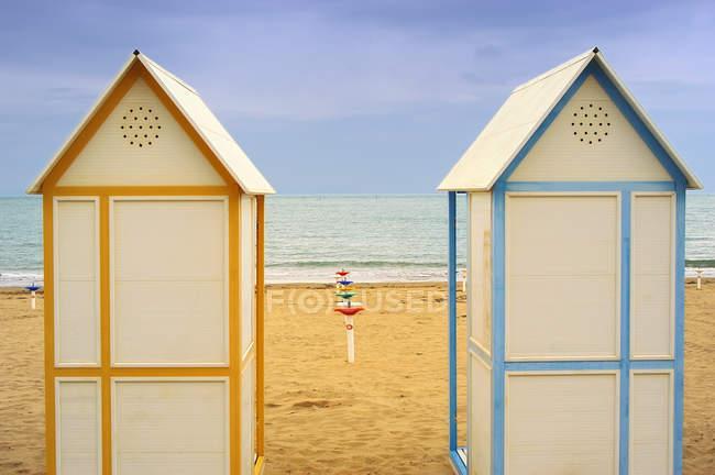Песчаный пляж в морской воде и две хижины — стоковое фото